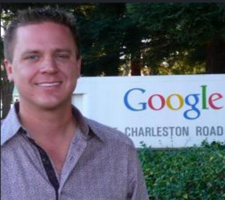 homem de camisa rosa em frente a placa da google